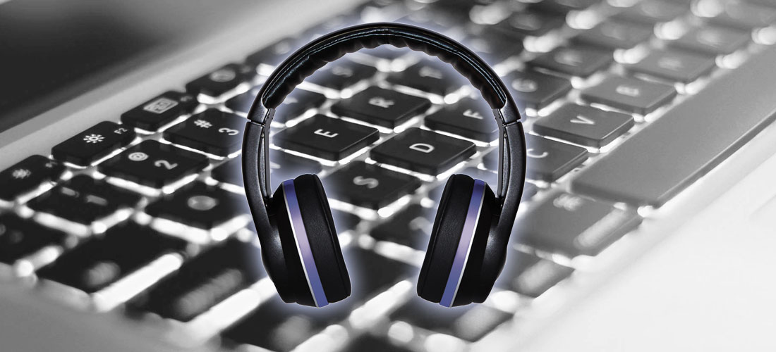 image of headphones in front of computer keyboard for audio transcription of focus groups, meetings, interviews and conference calls